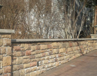 cultured stone wall lining to driveway