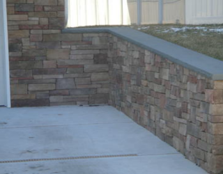 driveway with stone wall lining installed by pavers