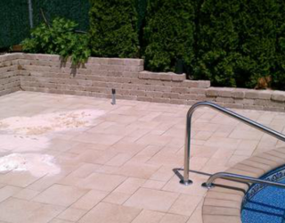 stone ground and wall installed by pool in backyard