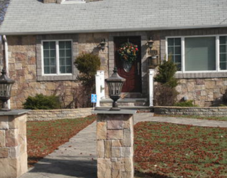 flag stone walkway and stone face house residential