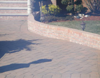 decorative residential walkway made with bricks and lined by bricks