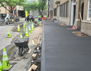 concrete pouring and paved by pavers near commercial building